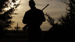 Hunter with rifle - Silhouette - Standing - Walk towards camera Stock Footage