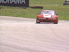 MotorsportsGT roadcourse race turn 6 follow shot oldsmobile red tight, very fast Stock Footage