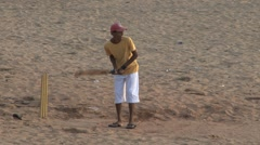 Kid playing cricket on the beach Stock Footage