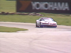 Motorsports, GT race turn 6 follow shot oldsmobile white tight Stock Footage