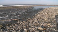 Wide pan of water flowing out of the Ventura River estuary into the Pacific Stock Footage
