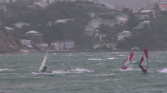 Windsurfer riding waves across a bay Stock Footage