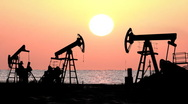 Working oil pumps silhouette against sunrise Stock Footage