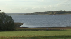Distant dinghy crosses Rutland Water. - stock footage