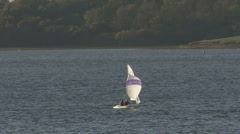 A dinghy sails across Rutland Water. - stock footage