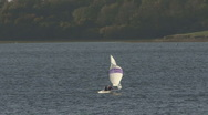 A dinghy sails across Rutland Water. Stock Footage