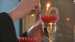 priest lights a candle Stock Footage