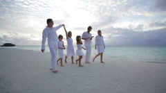 Family of six walking at sunset on the beach Stock Footage