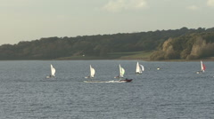 Dinghies racecaross Rutland Water, RIB speeds by. Stock Footage