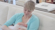 Caucasian mother breastfeeding baby on sofa Stock Footage