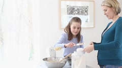 Expectant Caucasian mother and daughter baking in kitchen Stock Footage