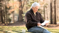 Smiling senior Caucasian man receiving good news in mail and showing paper to Stock Footage