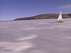 Extreme winter sport, Ice sail boat #3, alongside handheld from chase vehicle Stock Footage