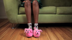 African American women on couch tapping her feet wearing pink rabbit slippers Stock Footage