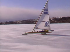 Extreme winter sport, Ice sail boat #2, alongside handheld from chase vehicle Stock Footage