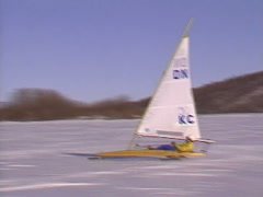 Extreme winter sport, Ice sail boat #1, alongside handheld from chase vehicle Stock Footage