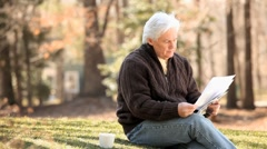 Senior Caucasian man reading paperwork and shaking head in frustration Stock Footage