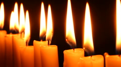 Candle light. Track beside a row of burning candles. - stock footage