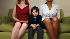 Happy young boy on couch with two  women Stock Footage