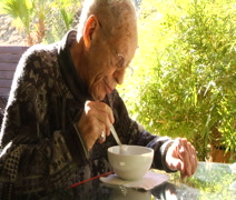 Elderly man eating breakfast outdoors in his backyard Stock Footage