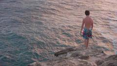 Cliff Diver - A Young Man Jumps from a Cliff into Ocean Below Stock Footage