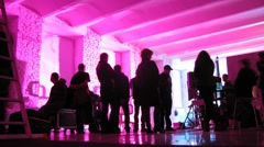 People walk inside pink lit room while filming video clip Stock Footage
