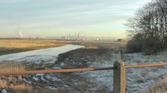 Oil Refinery across nature reserve, frozen creek and frost on grass Stock Footage