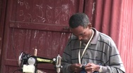 Man sewing in African shanty town Stock Footage