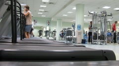 People run on treadmills at Multisport fitness club Stock Footage