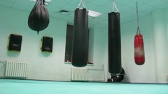 Man dressed in white hit four different punchbags Stock Footage