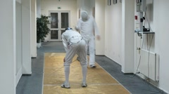 Two men finish their fencing at Multisport fitness club Stock Footage