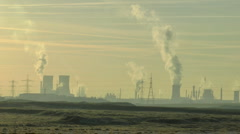 Cooling towers emitting steam with Electric pylons - Long shot across fields - stock footage