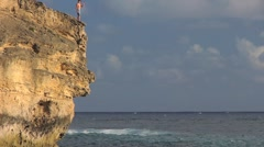 Young Man Jumping off Cliff into Ocean Stock Footage