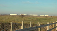 Stock Video Footage of Industrial Storage Tanks across fields