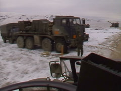 Military, riding on-board AFV passing artillery fire position Stock Footage