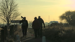 Bird Watchers walk away from the camera along a path beside a busy road Stock Footage