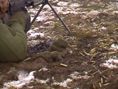 Military, soldier firing GPMG, smoking casings on the cold ground Stock Footage
