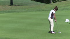 Female golfer sinks putt - stock footage