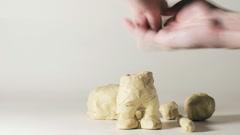 timelapse sculptor modeling plasticine comic figure of man in hat - stock footage