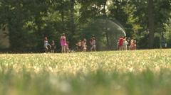 Kids play in a sprinkler - stock footage