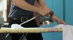 Chores at home: man ironing shirt - stock footage