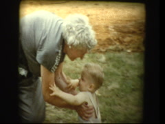 Cute blonde baby boy and elderly Grandmother hug and kiss Stock Footage