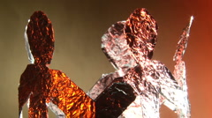 Aluminum people dance around Stock Footage