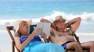 Aged couple relaxing on beach chairs Stock Footage