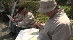 Cherry blossom Hanami Tokyo Ueno park old men painting Stock Footage