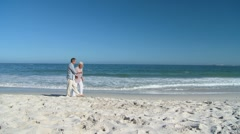 Elderly man walking on the beach wither his wife - stock footage