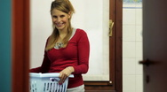 Chores: beautiful young woman using washing machine Stock Footage