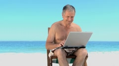 Mature man using a laptop sitting on beach chairs Stock Footage