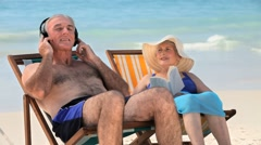 Man listening to music sitting on beach chairs with his wife Stock Footage