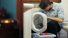 Man using washing machine and doing chores Stock Footage